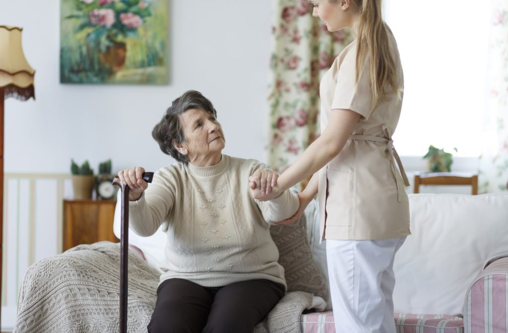 A senior woman standing up off of the couch with help from a supporting nurse